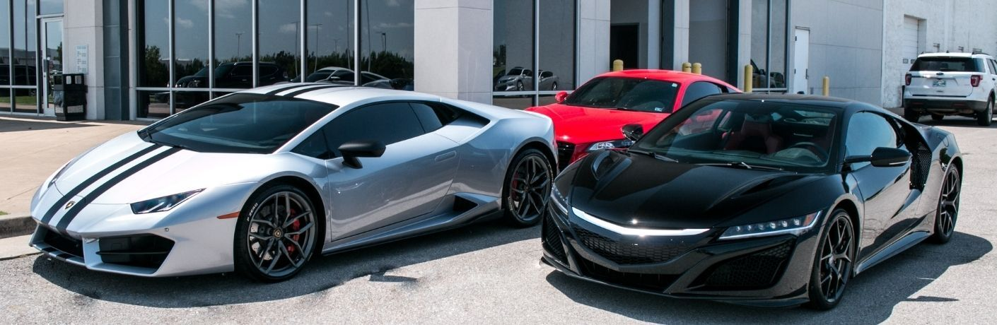 Three luxury cars parked outside the Battison Honda showroon