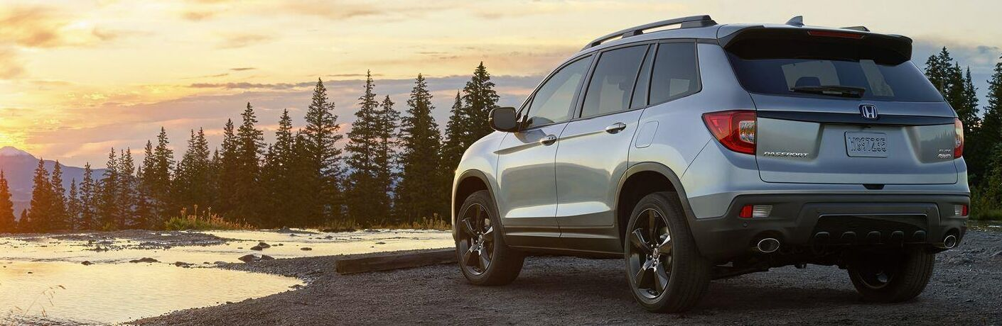 2019 Honda Passport exterior back fascia and drivers side on lake shore with pine trees