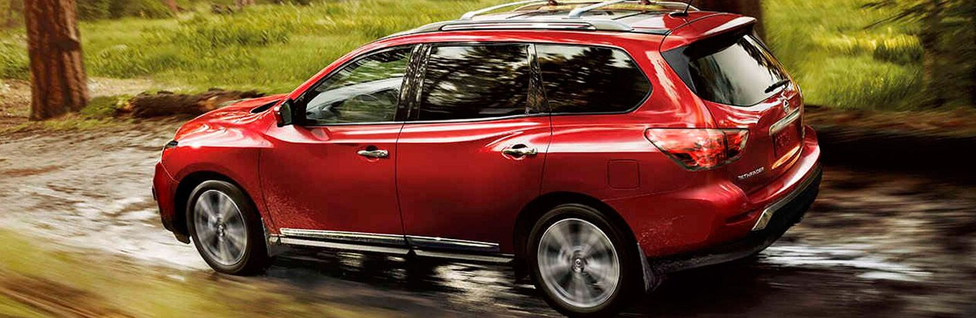 red 2017 Nissan Pathfinder driving through forest