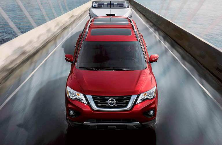 red 2017 Nissan Pathfinder towing boat across bridge
