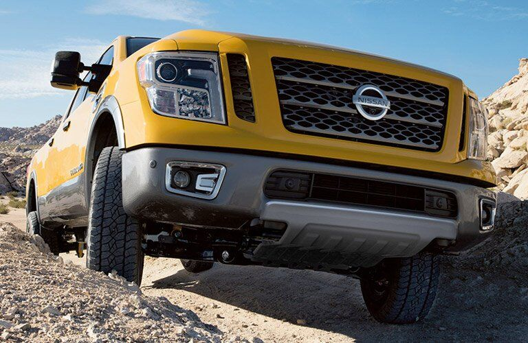 yellow 2017 Nissan Titan XD driving on top of rocks