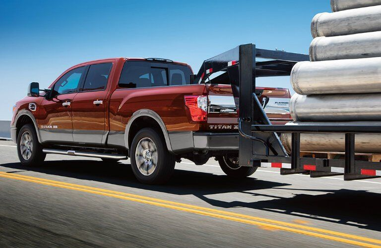 red 2017 Nissan Titan XD towing construction equipment