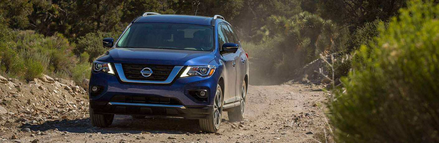 blue 2017 Nissan Pathfinder driving through desert