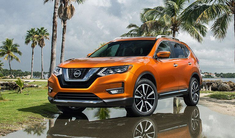 orange 2017 Nissan Rogue in front of palm trees