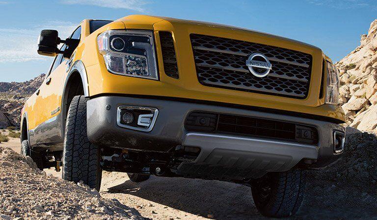 yellow 2017 Nissan Titan XD driving on top of rocks