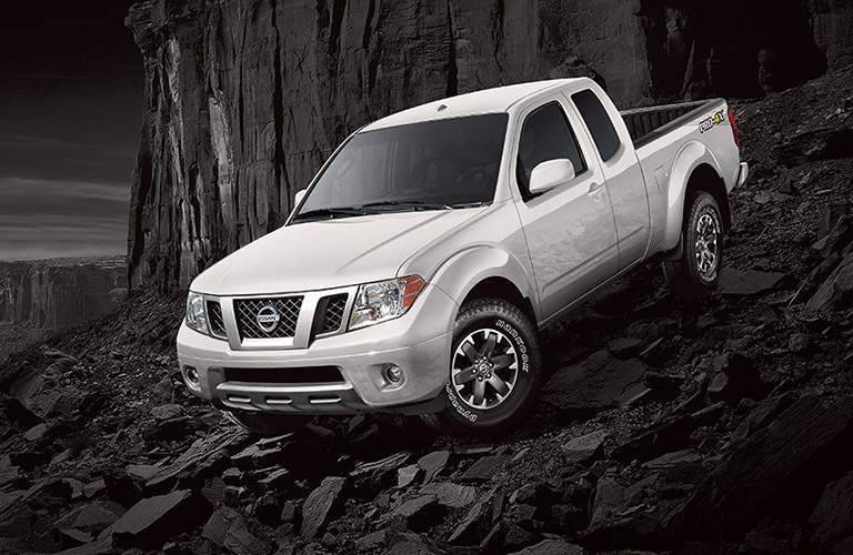 Exterior view of the front of a silver 2018 Nissan Frontier parked on a black rocky hill