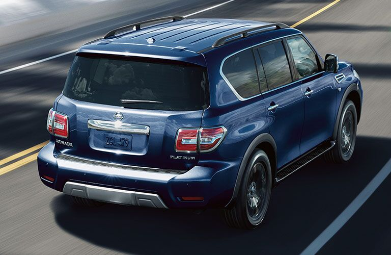 Exterior view of the rear of a blue 2018 Nissan Armada driving down a highway