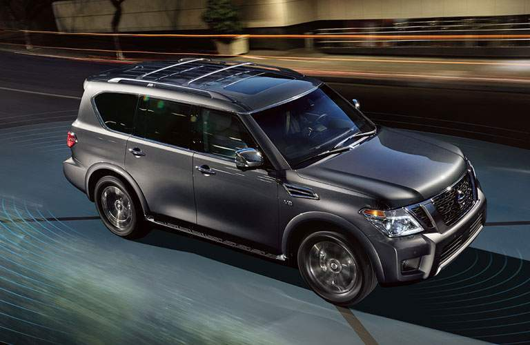 Exterior view of a dark gray 2018 Nissan Armada driving down a city street at night