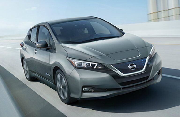 Exterior view of a gray 2018 Nissan LEAF driving on an overpass