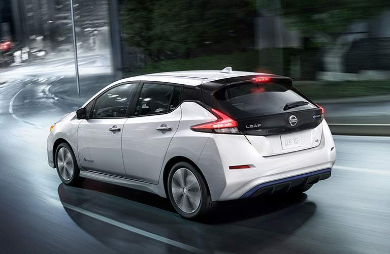 Exterior view of a white 2018 Nissan LEAF driving around a curve in a city street