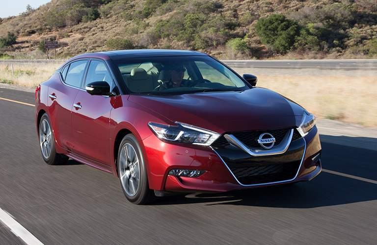 Exterior view of a red 2018 Nissan Maxima driving down a divided highway during the day