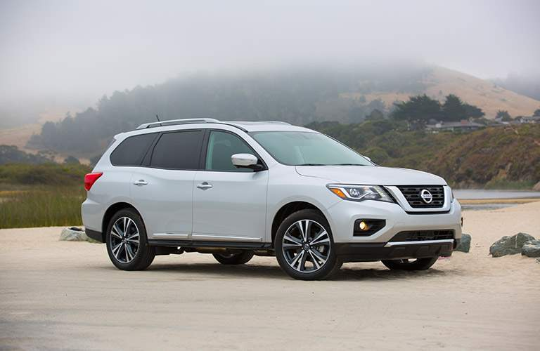 View of silver 2018 Nissan Pathfinder parked on sandy surface with mountains in background