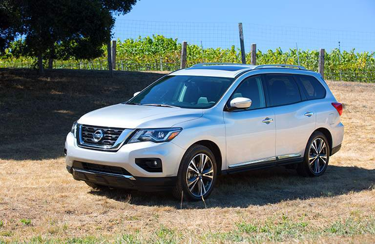 View of silver 2018 Nissan Pathfinder parked on grass with trees and farm land in background