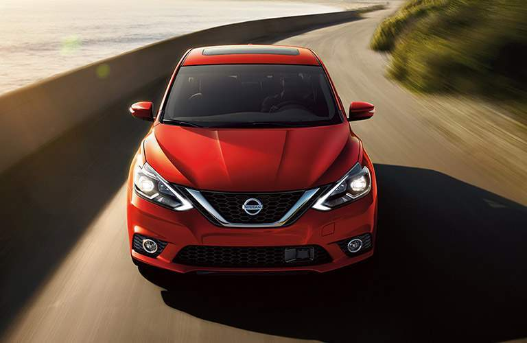 Exterior view of the front of a red 2018 Nissan Sentra driving down a waterfront road