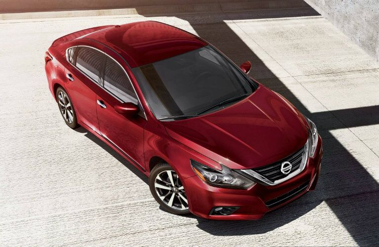Exterior view of a red 2018 Nissan Altima parked in an empty paved lot