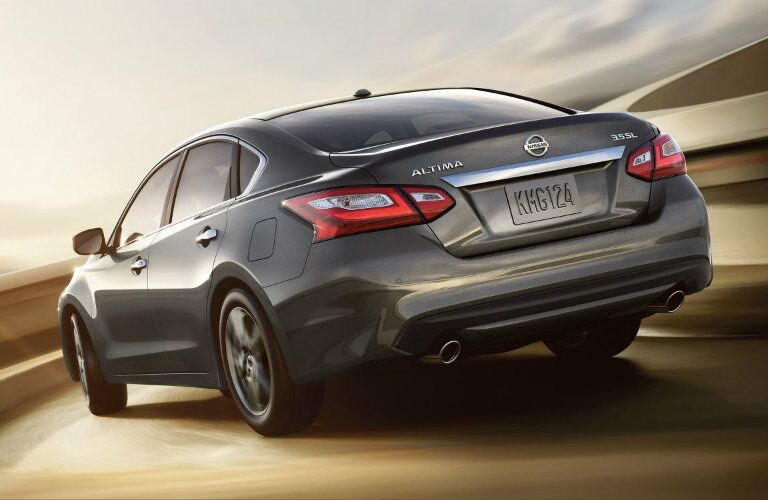 Exterior view of the rear of a gray 2018 Nissan Altima driving down an empty road