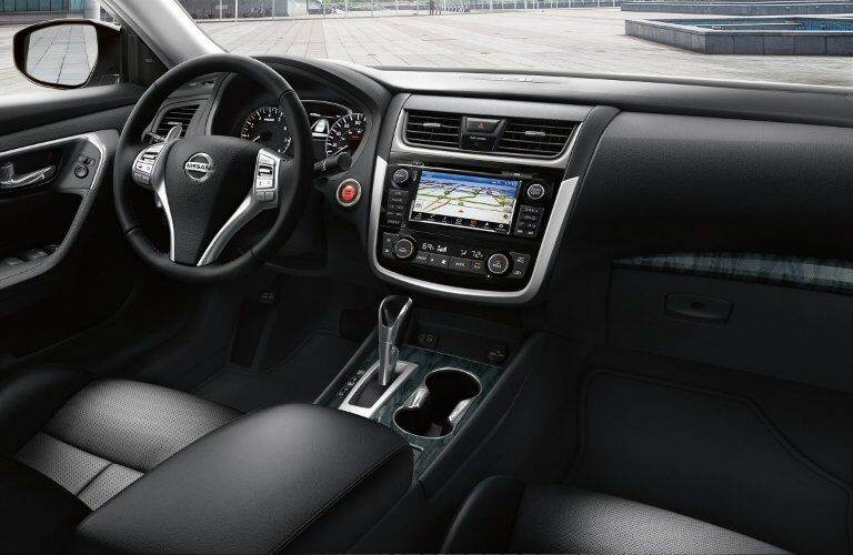 Interior view of black seating and dashboard with steering wheel and touchscreen in a 2018 Nissan Altima