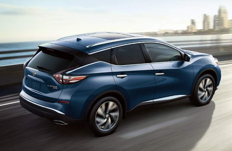 Exterior view of the rear of a blue 2018 Nissan Murano driving down a highway