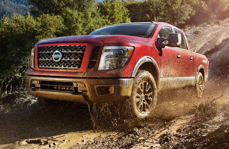 Exterior view of a 2018 Nissan TITAN driving through muddy terrain