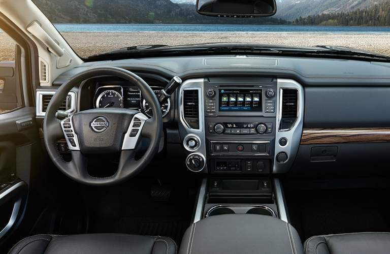 Interior view of the black steering wheel and touchscreen of a 2018 Nissan Titan
