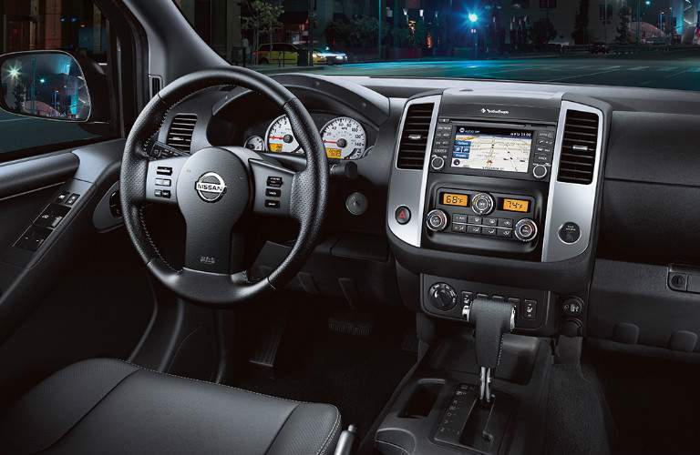 View of 2018 Nissan Frontier interior showing steering wheel and infotainment system with touch panel