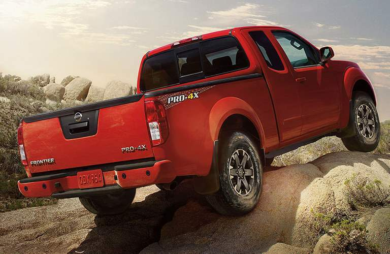 Exterior view of the rear of a red 2018 Nissan Frontier parked on a rocky hill
