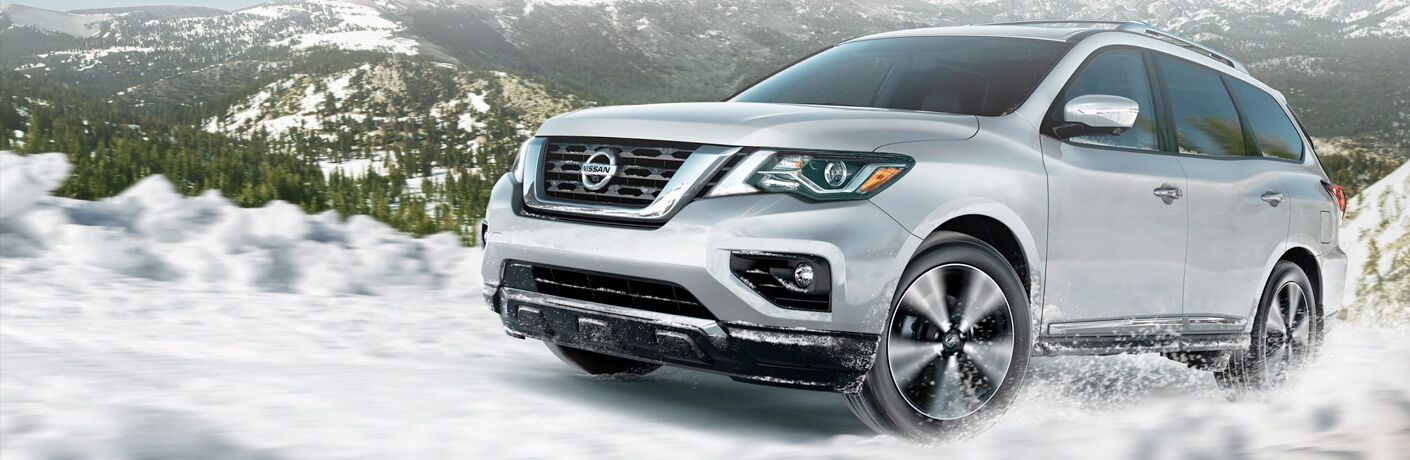 Exterior view of a silver 2019 Nissan Pathfinder driving through deep snow