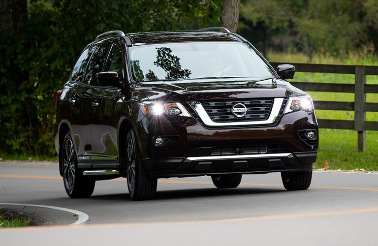 Exterior view of brown 2019 Nissan Pathfinder driving down a two-lane country road