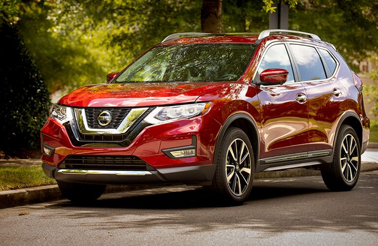 Exterior view of the front of a red 2019 Nissan Rogue parked on a street in the suburbs