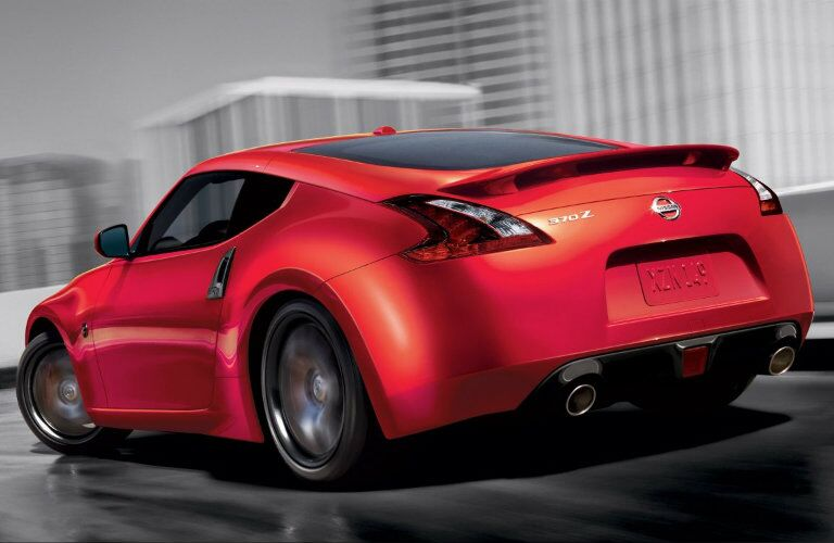 Exterior view of the rear of a red 2019 Nissan 370Z driving down a city expressway
