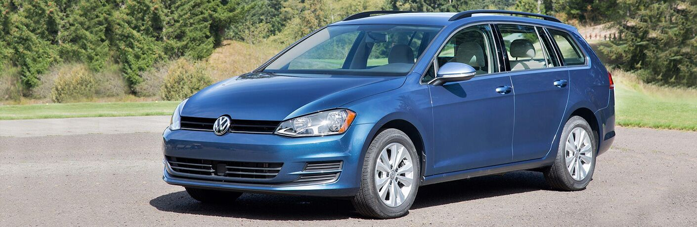 2018 VW Golf SportWagen in Silk Blue Metallic parked in front of grassy hill