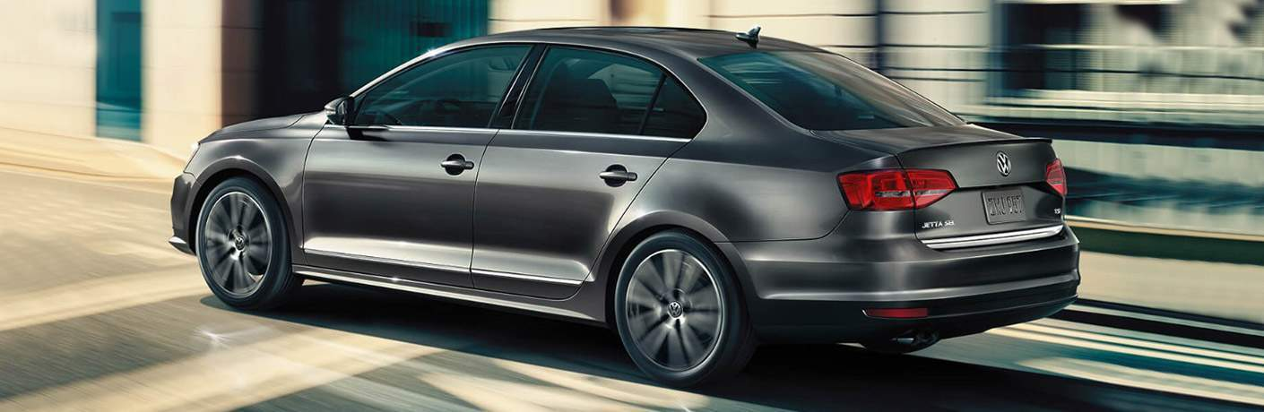 side profile of gray 2018 Volkswagen Jetta driving on city street