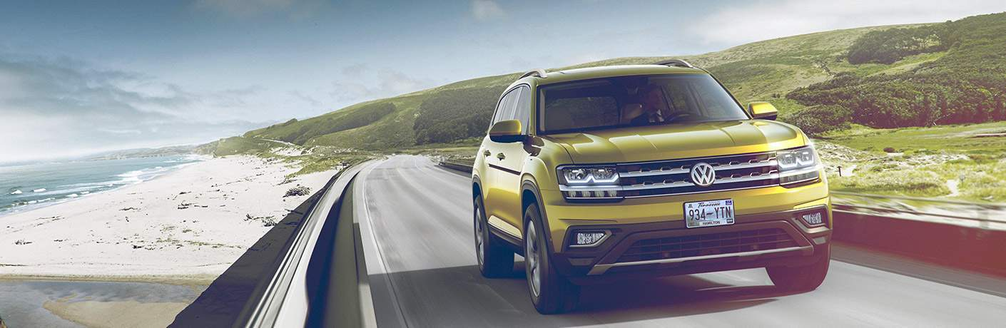 2018 Volkswagen Atlas yellow front on road by beach