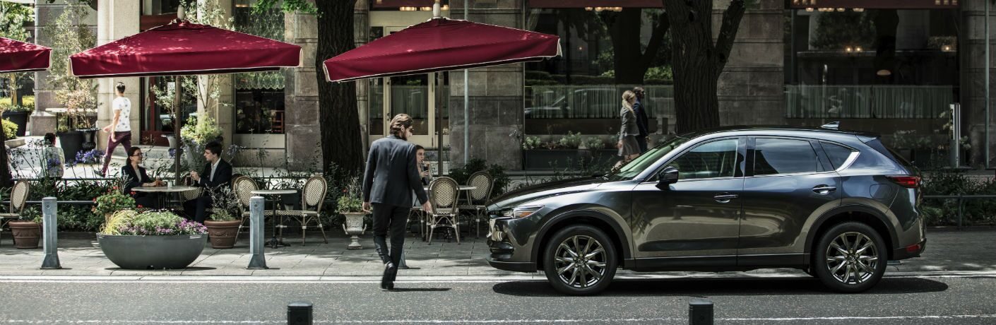 A left profile photo of the 2019 Mazda CX-5 parked in front of a restaurant.