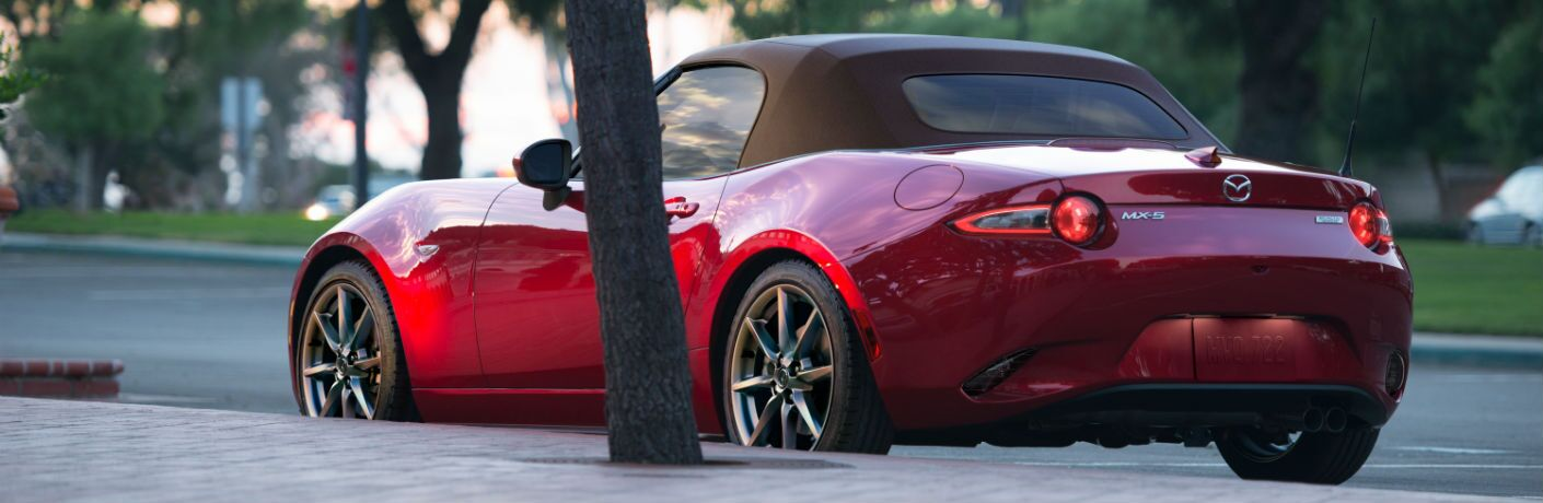 A left rear quarter photo of the 2019 Mazda MX-5 Miata parked on the street.