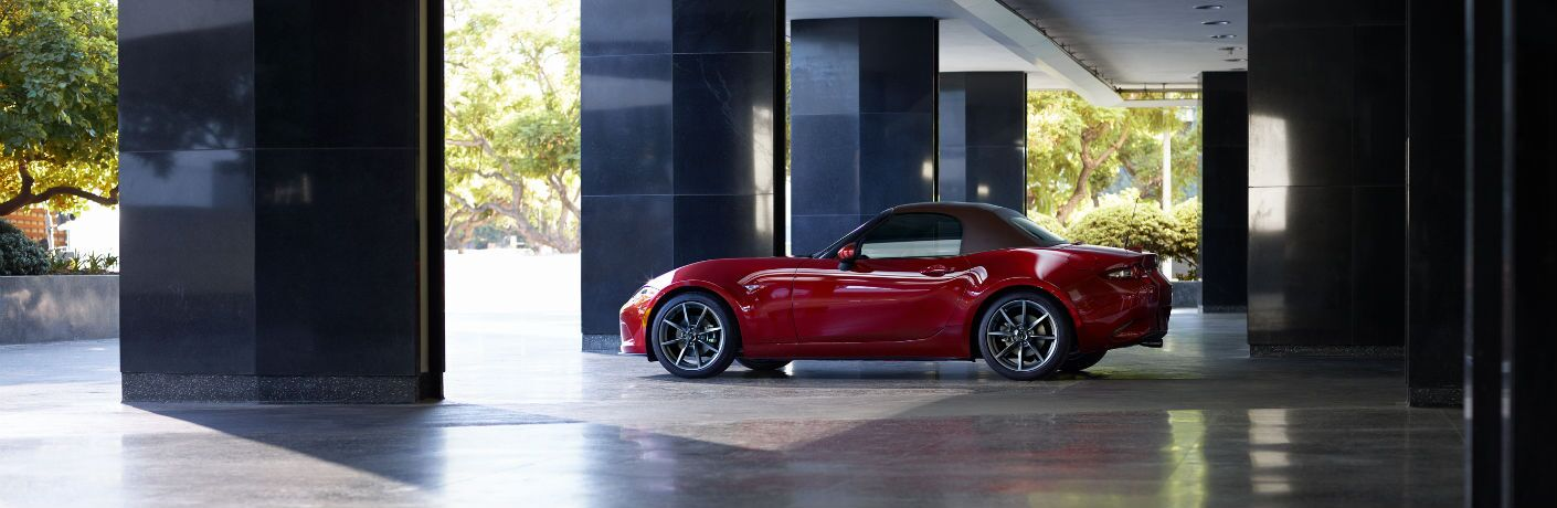A left profile photo of the 2019 Mazda MX-5 Miata parked under a building.