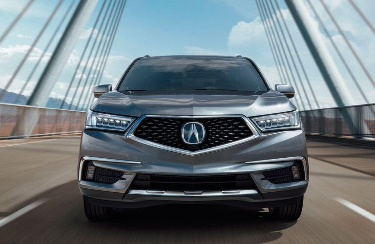 Front view of silver Acura MDX driving over bridge