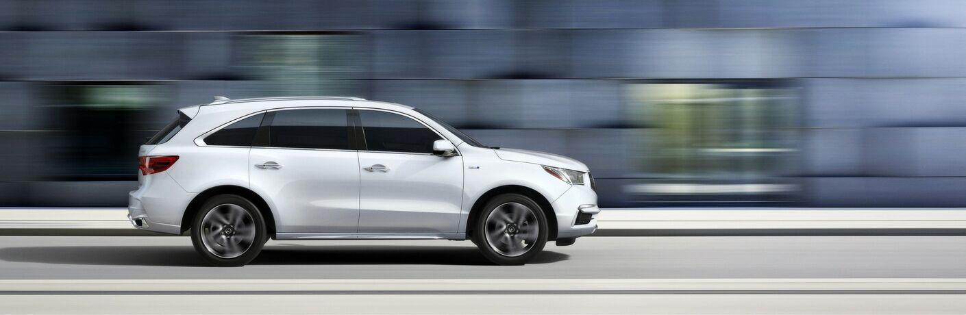 side profile of white Acura MDX driving