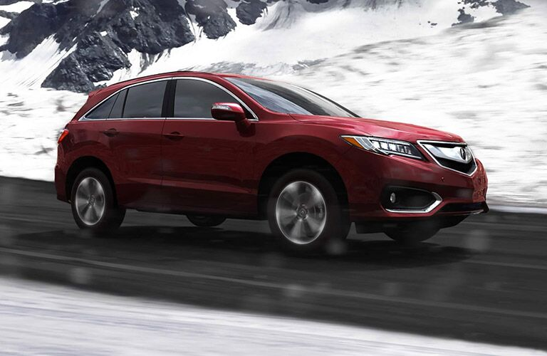 Red 2017 Acura RDX driving on snowy mountain road