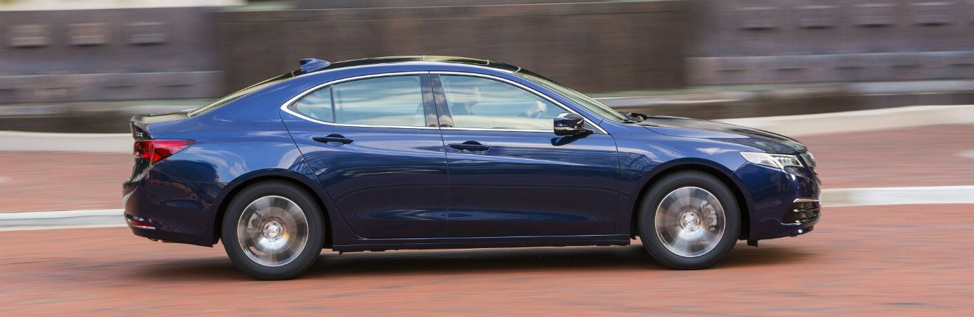 Profile view of blue 2017 Acura TLX driving on city street