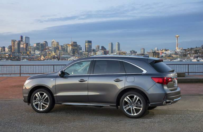side profile of gray 2018 Acura MDX Sport Hybrid with city skyline in background