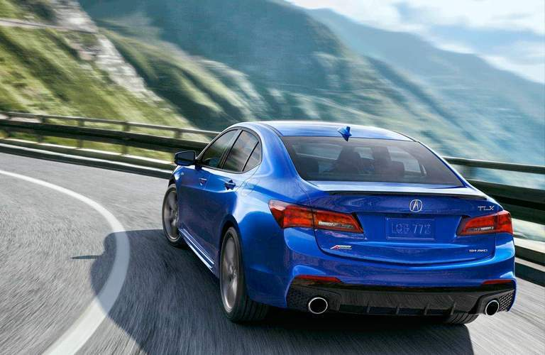 rear of blue Acura TLX rounding corner on mountainous road