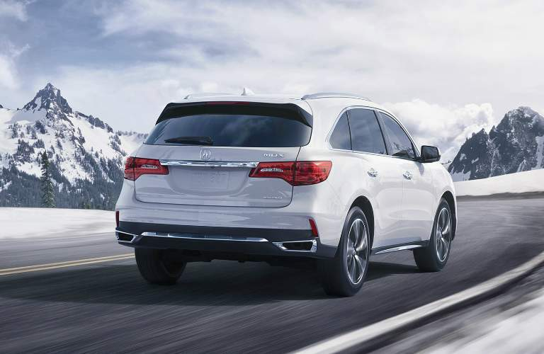 rear view of white 2018 Acura MDX driving in winter