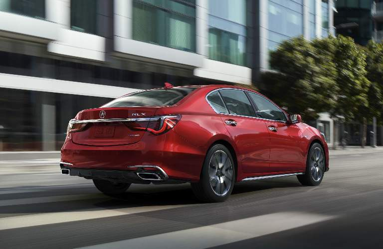 red 2018 Acura RLX driving on city street, rear side profile