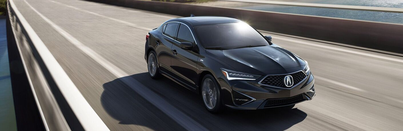 Black 2019 Acura ILX driving on bridge over water