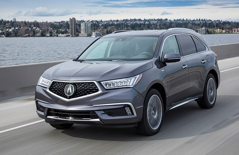 front-side view of gray 2019 Acura MDX driving across bridge