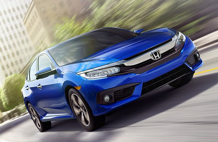 Exterior view of a blue 2018 Honda Civic driving down a city street