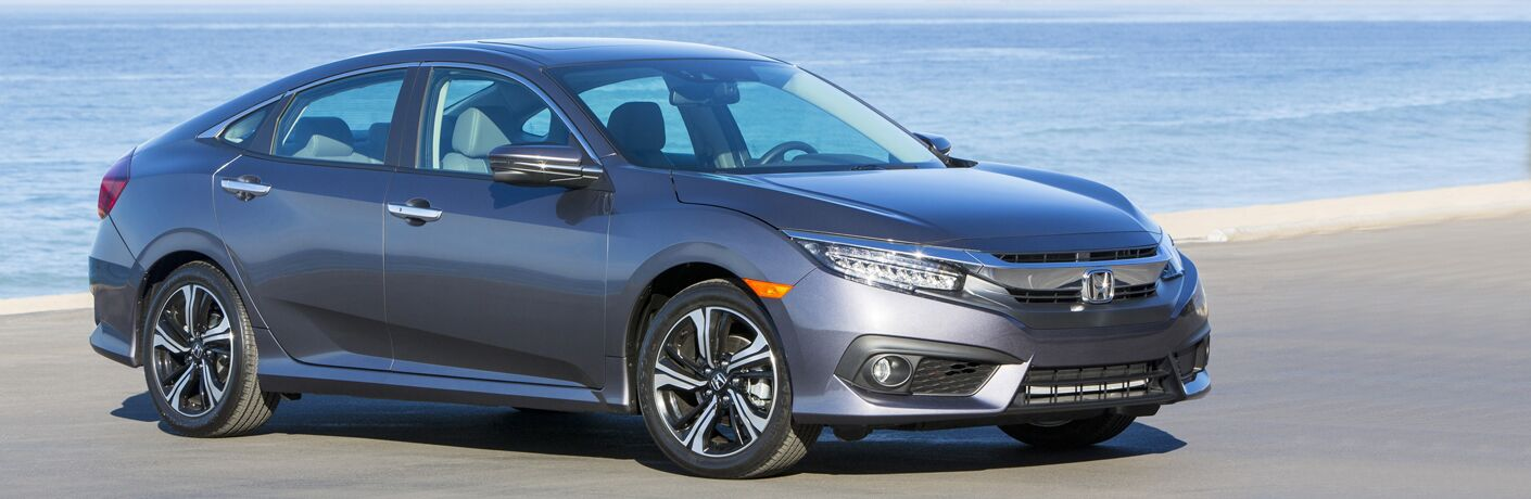 Exterior view of a gray 2018 Honda Civic parked near a beach with water in background