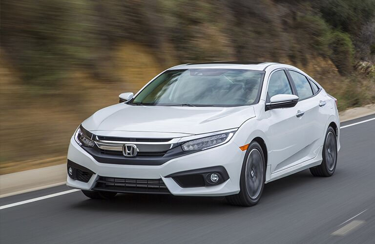 Exterior view of a white 2018 Honda Civic driving down highway with trees in background