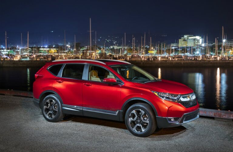 red 2018 Honda CR-V parked by river at night with lights across the water